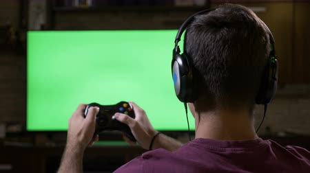playstation : Teenager with earphones using game controller in front of green screen TV playing a solo action game