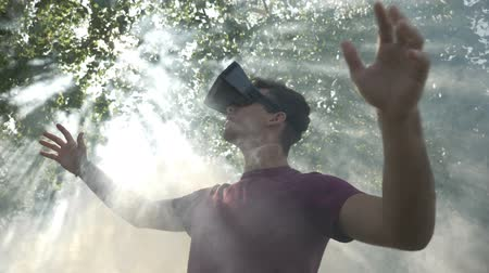 realidade : Slow motion of surprised young man with VR goggles feeling excited by virtual reality simulation exploring immersive cyberspace with smoke