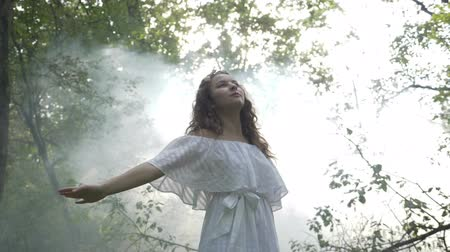 enchanted princess : Mysterious angelic girl in white dress spinning amongst the trees in the forest