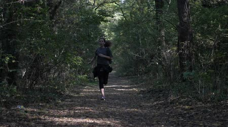 stay active : Slow motion young slim girl training in the forest on an autumn day to stay healthy and in good shape