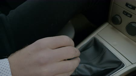 gearstick : Hand of man shifting gears in a driving car
