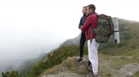поход : Young couple of tourists kissing on the edge of mountain enjoying the amazing valley panorama with forest shrouded in thick fog
