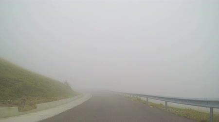 imprudence : Car running high speed time lapse on bad visibility along mountain road on foggy weather