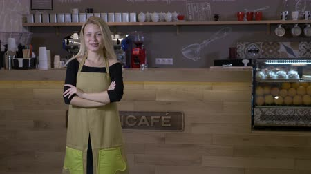 végre : Hard working young blonde woman finally opens her own cafe business and stands proudly in front of the counter with arms crossed and smiling