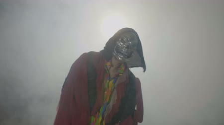 possessed : Possessed creature wearing a scary mask celebrating day of the dead on a foggy smoke background