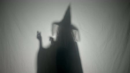 ведьма : Shadow silhouette of an evil witch dialing a phone number laughing and cursing on the phone on Halloween day Стоковые видеозаписи