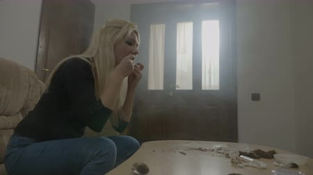 being fired : Beautiful young blonde woman rolling a marijuana cigarette at home and smoking it to calm down after being fired from work Stock Footage