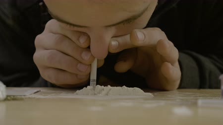 snorting : Close up of a narcotic young father snorting cocaine from the table while his wife and children are not home Stock Footage