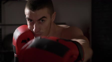 into focus : POV close up of an athletic muscular kickboxer looking into the camera while he shadow boxes in slow motion Stock Footage