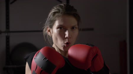 into focus : POV close up of beautiful female model looking into the camera and shadow boxing in slow motion Stock Footage