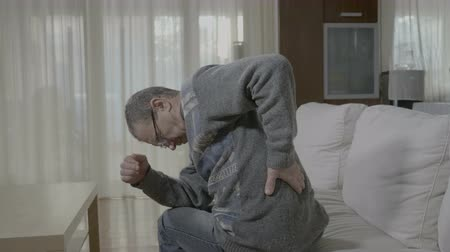 mężczyźni : Elderly ill man with rheumatism stretching and massaging his back having a painful cramp