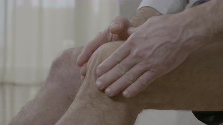diseased : Old man massaging his arthritic knee having joint ache at home Stock Footage