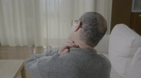 pained : Old man in pain massaging his back neck having a muscle cramp or column spinal discomfort