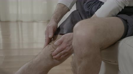 feszült : Elder man suffering from rheumatic pain disease rubbing his sore and painful knee doing herself massage therapy