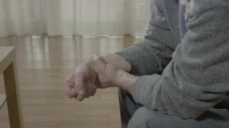 az érintett : Closeup of old man with arthritis touching his painful wrist having rheumatism sitting on the couch at home