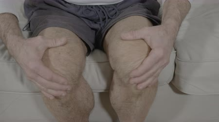 self injury : Closeup of aged man leg with osteoarthritis doing self relaxation massage reducing stiffness of knee Stock Footage