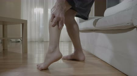 pained : Closeup of barefoot senior man having muscle discomfort on leg while he standing up from couch