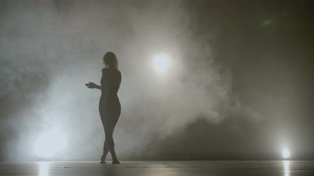 Young fit girl dancing on a smoke background while recording a music video clip for a famous singer