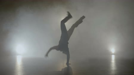 Young teenage hip hop male break dancer dancing on a set with smoke while filming for a famous pop music band Stock Footage