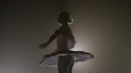 Young beautiful ballerina student spinning and performing dancing tricks on a smoke dark background