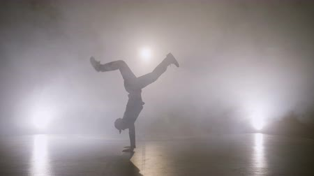 Attractive boy performing breakdance dancing tricks on the stage while auditioning for a music video clip Stock Footage