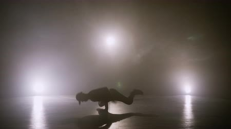 Hip hop male dancer with cap performing breakdancing tricks on the floor with smoke in the background