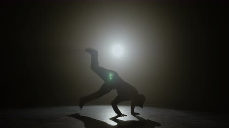 Professional break dancer dancing on a stage with spotlight in the background