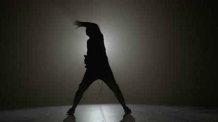 Silhouette of a young man in hood performing hip hop moves on a stage with spotlight in the background