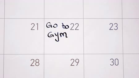 Animation writing go to gym marking the day in calendar with black ink Stock Footage
