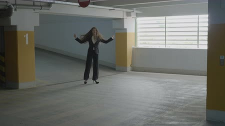 humor : Young beautiful business woman funny dancing and jumping joyfully in a underground parking lot to express her happiness