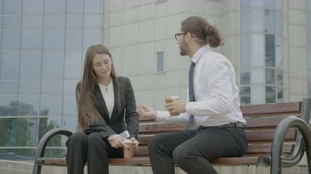 Young business woman listening to her businessman colleague on the bench in front of the corporate building while trying to leave