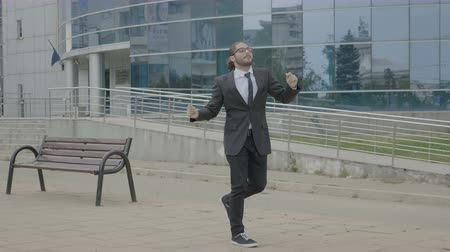 Young modern businessman in suit and tie leaving work and funny dancing joyfully on his way home Stock Footage