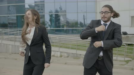 humor : Attractive businesswoman and business man employees wearing formal clothes funny dancing like crazy outside the corporation after leaving work