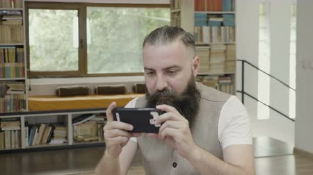 ator : Business man with beard wearing casual outfit sitting in the office looking at his smartphone reading and doing thumb up gesture
