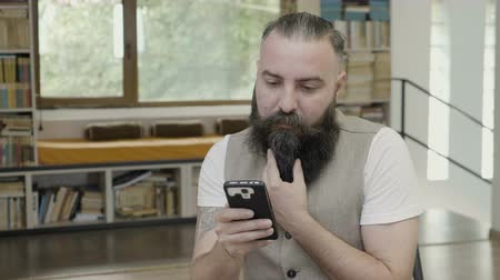 munkatársa : Reaction of a young man with beard reading something on his smart phone approving and nodding his head yes Stock mozgókép