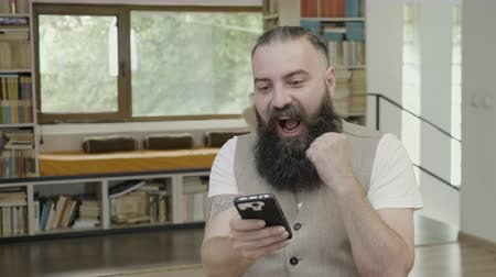 актер : Happy smiling business man with beard celebrating success and victory after scrolling his smart phone at the office Стоковые видеозаписи