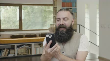 expressão facial : Business man with beard looking at a video on his smartphone and having a joyful supporting reaction making victory gesture with his hands