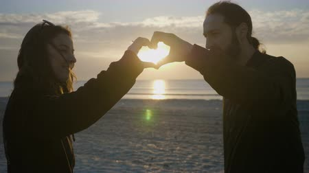 elkötelezettség : Teenage couple making a heart shape with their heads on the beach before sunset