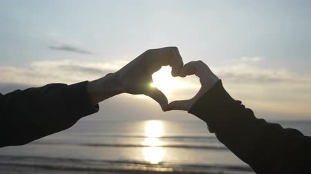 závazek : Close up of two lovers hand making a heart shape on a sunrise beach in slow motion