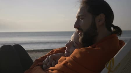 elkötelezettség : Close up of a young affectionate couple lying embraced on the lounge watching sunrise on the beach early in the morning covered with blanket in slow motion Stock mozgókép