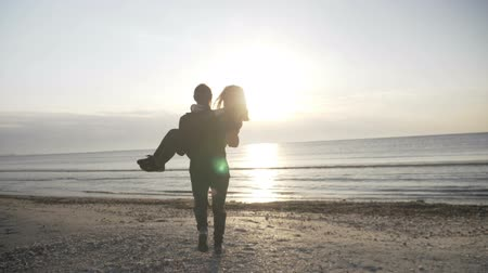 whirling : Young happy couple in love swirling on the beach man holding woman in his arms while sun goes down at sunset in slow motion Stock Footage