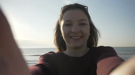 tomar : Smiling beautiful woman with sunglasses taking selfie using phone on the beach while spinning and enjoying the sea in slow motion Stock Footage
