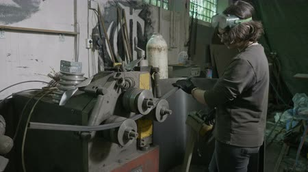 собственность : Woman blacksmith bending an iron bar using a professional metal bending machine in her own workshop Стоковые видеозаписи
