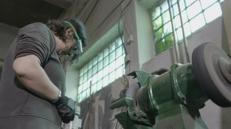 угловой : Woman blacksmith cutting a piece of metal from a screw using an angular grinding machine that makes sparkles in contact with it in an industrial factory