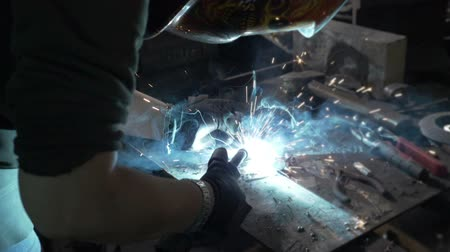 hangar : Young woman welder wearing protection mask and welding metal that makes a blue flame and a shower of sparkles in her workshop in slow motion