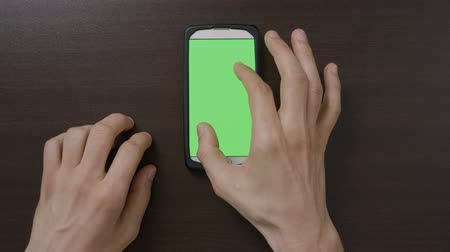 sürgülü : Male fingers making gestures touching and swiping the green screen of smartphone technology and social media networks addiction concept