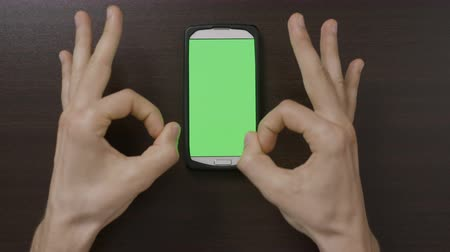 promover : Top view of millennial man hands gesturing in front of green screen smartphone evaluating the app applications with thumbs up OK heart fingers gesture