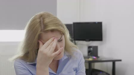 перегружены : Depressed young corporate employee suffering from headache feeling upset and fatigue at the office massaging her temples relieving the stress Стоковые видеозаписи