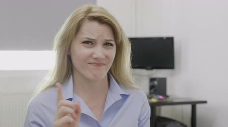 выражающий : Young business woman showing disagreement with negative no gesture with finger declining offer in her office Стоковые видеозаписи