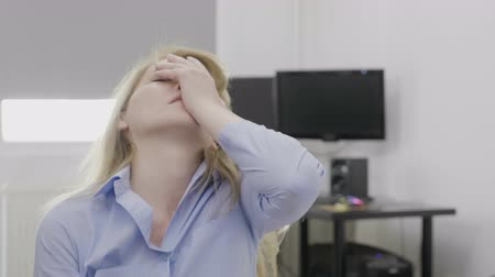 displeasure : Portrait of irritated young corporate woman at office slapping her face gesturing facepalm reaction expressing frustration Stock Footage
